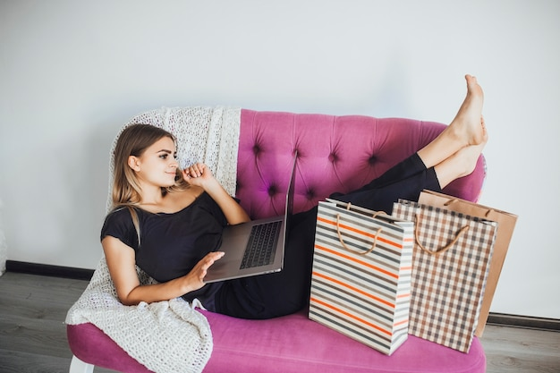Menina deitada no sofá com um laptop