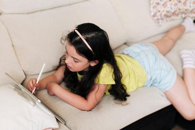 Menina deitada no sofá e desenhando no tablet