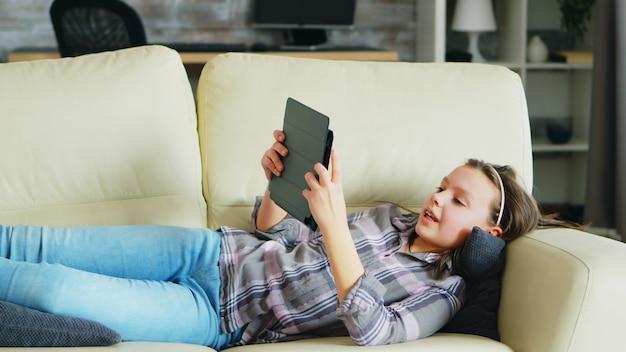 Menina deitada no sofá usando seu tablet. criança alegre.