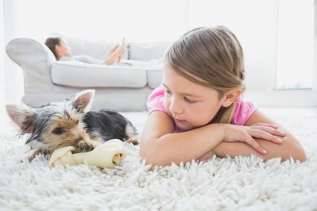Menina deitada no tapete com yorkshire terrier