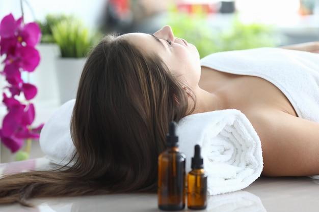 Menina deitada sob uma toalha após massagem com óleo