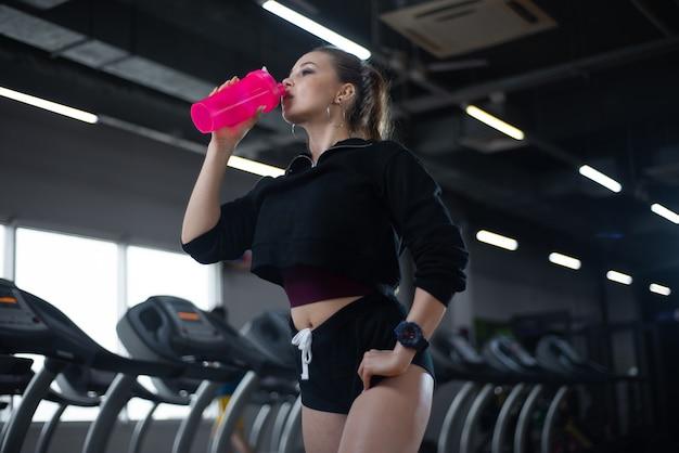 Menina depois de um treino de beber água no ginásio