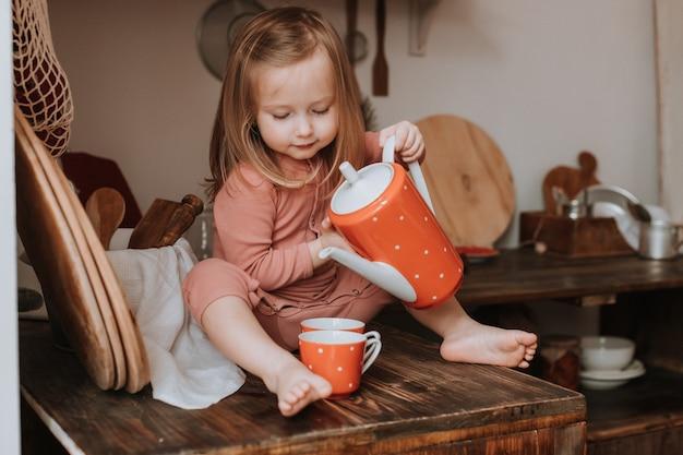Menina derrama chá em uma caneca de um bule de cerâmica vermelha na cozinha de madeira de ervilhas