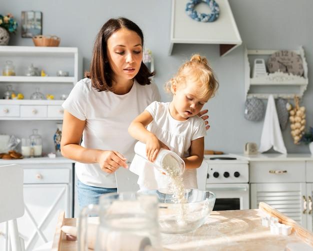 Menina derramando farinha em uma tigela