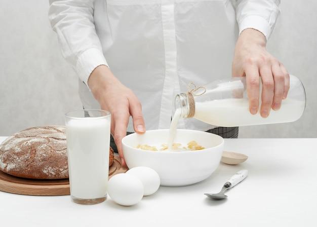 Menina derramando um pouco de leite em uma tigela com cereais