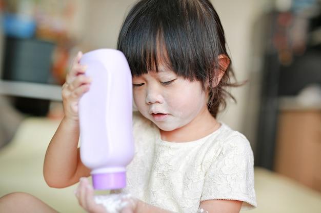 Menina derramar o talco para a mão