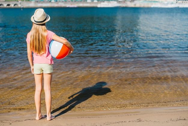 Menina descalça com bola de vento, olhando a água