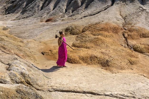 Menina descalça com um sári caminhando pelo deserto com uma enxada no ombro