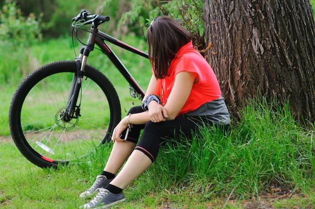 Menina descansando depois de andar de bicicleta perto de uma árvore