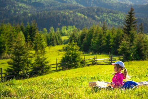 Menina descansando e sentado em um prado verde