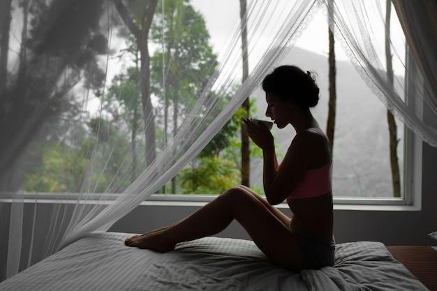 Menina descansando e tomando chá na cama com vista para a montanha na ilha sri lanka