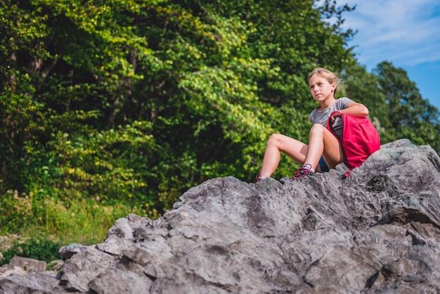 Menina descansando em uma pedra