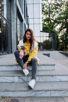 Menina descansando na escada. garota atraente elegante alegre moderno hippie andando pelas ruas da cidade.