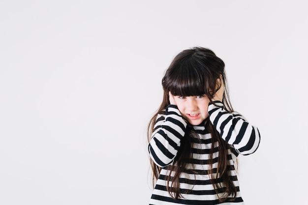 Menina descontente, cobrindo as orelhas
