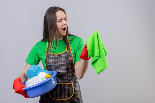 Menina descontente com a limpeza de uniforme com luvas vermelhas, segurando as gemas de limpeza e olhando para um pano na mão na parede branca isolada