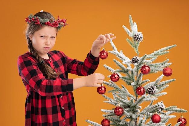 Menina descontente usando guirlanda de natal em vestido xadrez, decorando uma árvore de natal com rosto carrancudo em pé sobre uma parede laranja