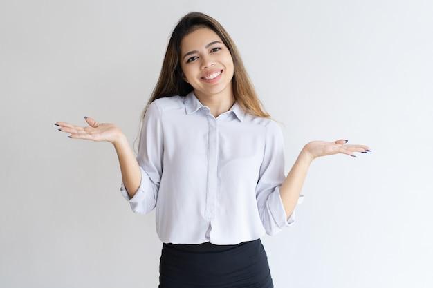 Menina descuidada alegre que shrugging ombros