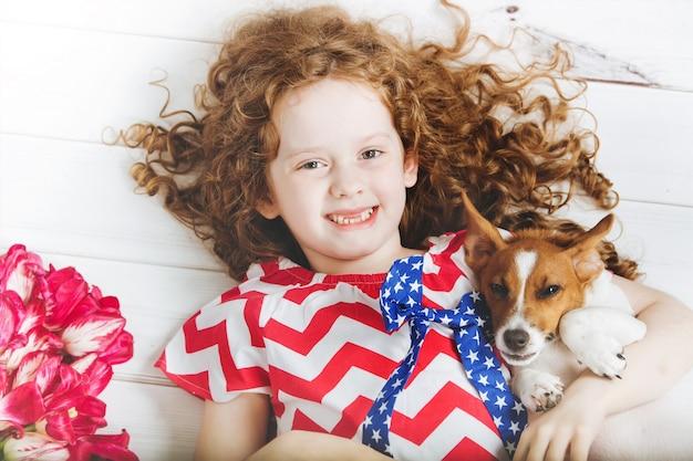 Menina desdentado de riso que abraça um cachorrinho.