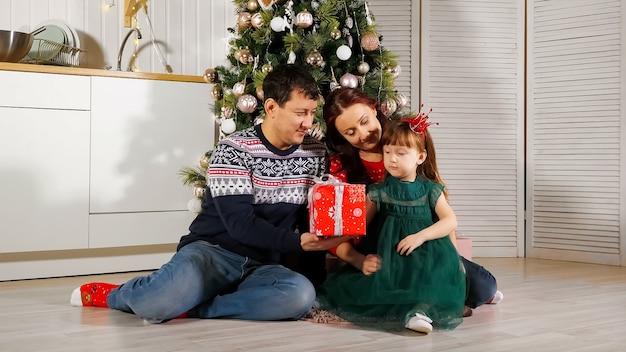 Menina desembrulhando caixa de presente com os pais perto da árvore de natal
