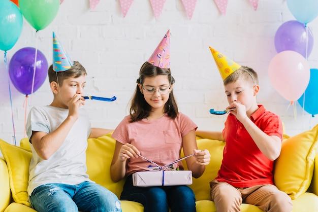 Menina desembrulhando presente de aniversário, enquanto seus amigos soprando chifre de festa