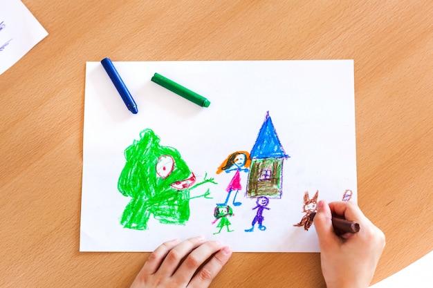 Menina desenha a imagem de um monstro atacando sua família. desenho com papel de giz de cera