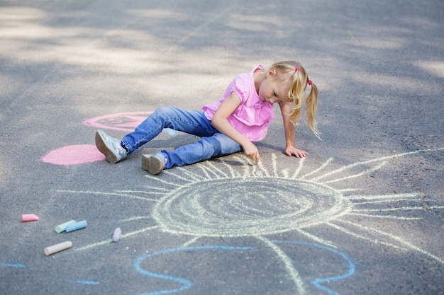 Menina desenha com giz na calçada