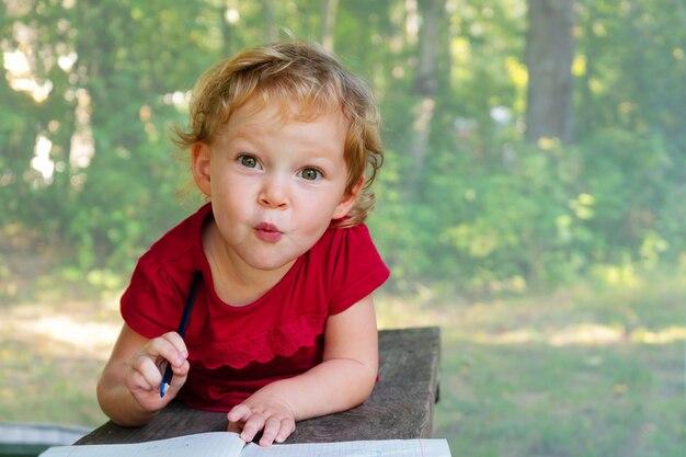 Menina desenha em um caderno sobre um fundo de natureza. o rosto bonito e emocional de uma criança de três anos.