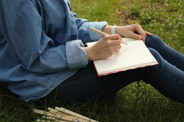 Menina desenha sentado ao ar livre na grama verde. conceito de criatividade