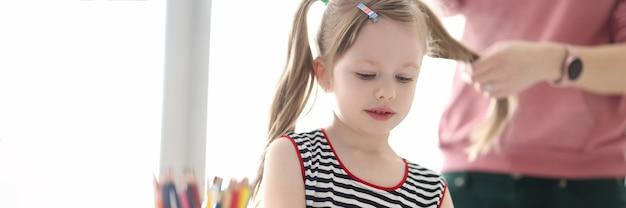 Menina desenhando com lápis mãe fazendo tranças no cabelo da criança