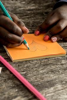 Menina desenhando e colorindo a forma de um coração em papel post-it laranja