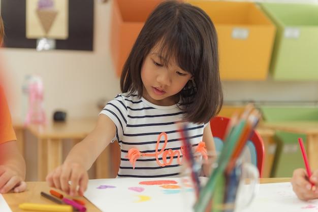 Menina desenhando lápis de cor na sala de aula do jardim de infância, conceito de educação pré-escolar e infantil, imagens de estilo vintage effective.