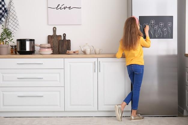 Menina desenhando no quadro-negro na cozinha