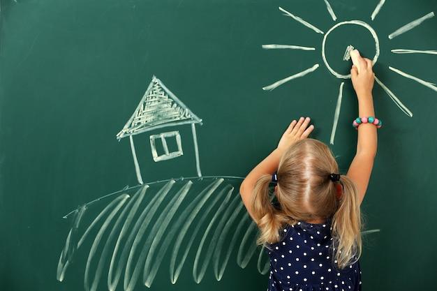 Menina desenhando no quadro-negro