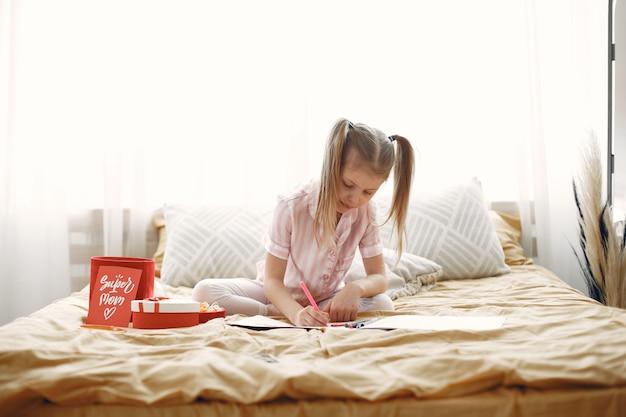 Menina desenhando sentada na cama com presentes