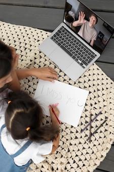 Menina desenhando uma mensagem de saudades para o pai dela