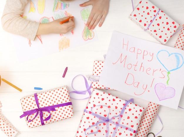 Menina desenho cartão de feliz dia das mães com presentes na mesa. plano de fundo do dia das mães
