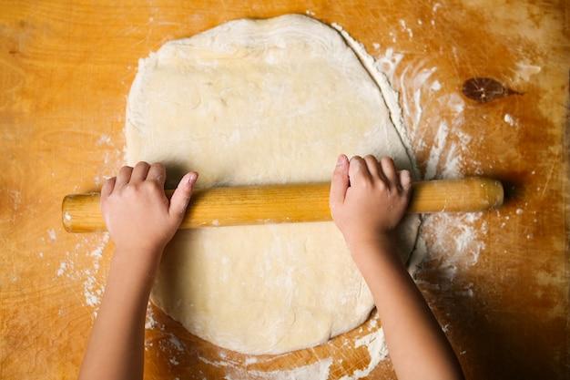 Menina desenrola a massa da pizza com o rolo na mesa de madeira.