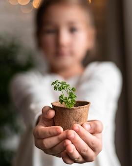 Menina desfocada segurando uma planta em um vaso em casa