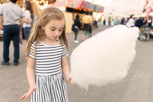 Menina, desfrutando de algodão doce no parque