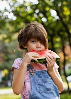Menina, desfrutando de melancia ao ar livre