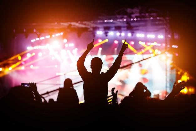 Menina desfrutando de um festival de música ou concerto. silhueta negra da multidão.