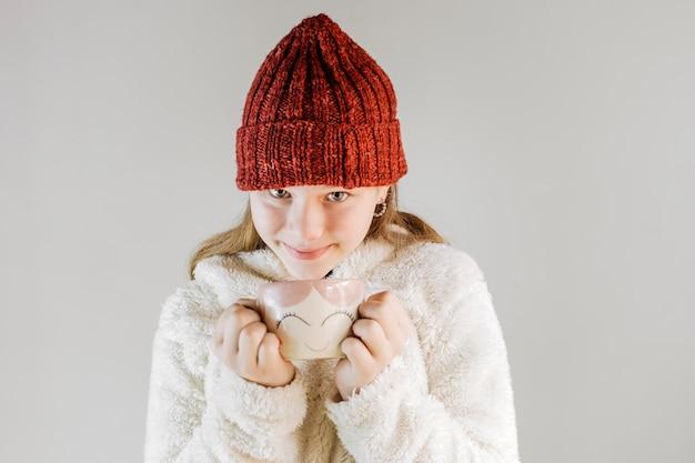 Menina, desgastar, tricote chapéu, segurando, xícara café