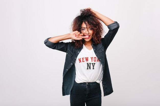 Menina deslumbrante magro com penteado africano e manicure vermelha gastando tempo. retrato interior de uma adorável jovem com pele bronzeada, posando com prazer.