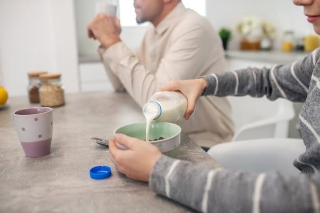 Menina despejando leite de uma garrafa em um prato com mingau, sentado à mesa e tomando café da manhã com o pai.