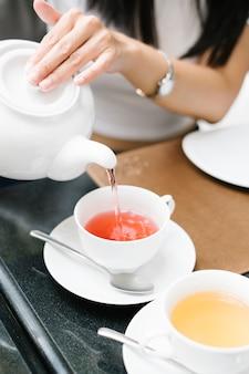 Menina despeje o chá lentamente