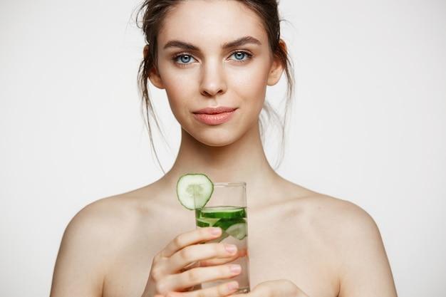 Menina despida bonita nova com pele limpa perfeita que sorri olhando a câmera que guarda o copo de água com fatias do pepino sobre o fundo branco. tratamento facial.