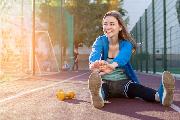Menina desportiva aquecendo em uma esteira, ginasta mulher malhando ao ar livre no sportswear, cópia espaço