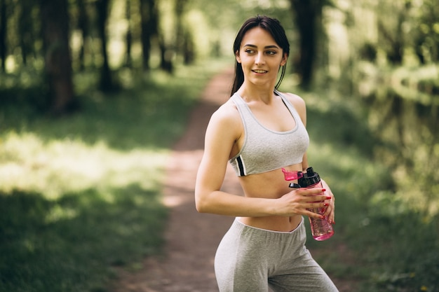 Menina desportiva bebendo água no parque