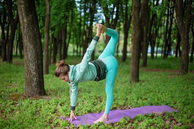 Menina desportiva bonita fina em pé em pose de meia-lua, exercício de ardha chandrasana em um parque de verão