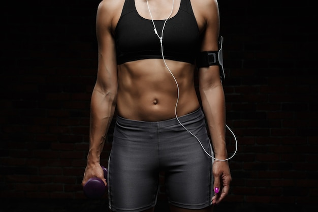 Menina desportiva bonita nova que treina sobre o fim escuro da parede acima.